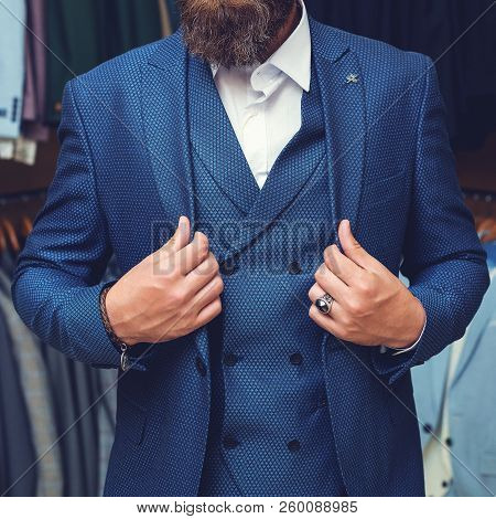 Man In Elegant Custom Tailored Expensive Suit Posing In Front Of Background. Perfect To Last Detail.