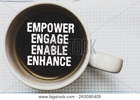 Writing note showing Empower Engage Enable Enhance. Business photo showcasing Empowerment Leadership Motivation Engagement Coffee mug with black coffee floating some white texts on white paper. poster