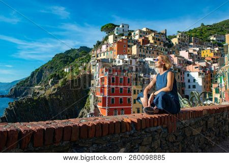 Woman sitting and looking at Mediterranean Sea in Riomaggiore, Cinque Terre, Ligurian coast of Italy, Europe. Stunning landscape with deep blue sea, clean sky and  colorful buildings on hills.