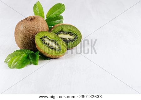 Ripe Kiwi With Juicy Slice And Drop Juice, Green Young Leaves On White Soft  Wood Board. Fresh Summe