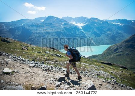 Hiker With Backpack Walking On Besseggen Ridge Over Gjende Lake In Jotunheimen National Park, Norway