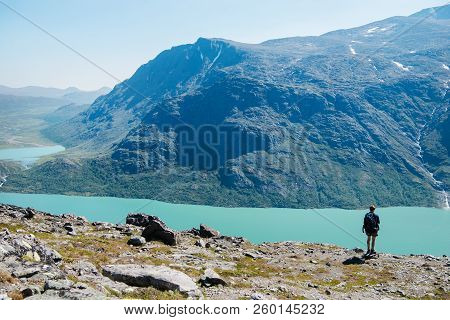 Hiker Standing On Besseggen Ridge And Looking At Gjende Lake In Jotunheimen National Park, Norway