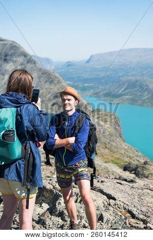 Woman Taking Photo Of Man On Besseggen Ridge In Jotunheimen National Park, Norway