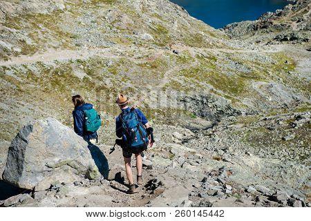 Couple On Travelers Hiking On Besseggen Ridge In Jotunheimen National Park, Norway