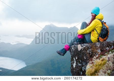 Image of tourist woman with backpack sitting on top of mountain in background of picturesque landscape