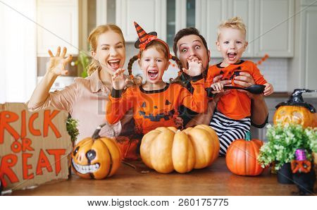 Happy Halloween! Family Mother Father And Children Cut A Pumpkin For Holiday Home