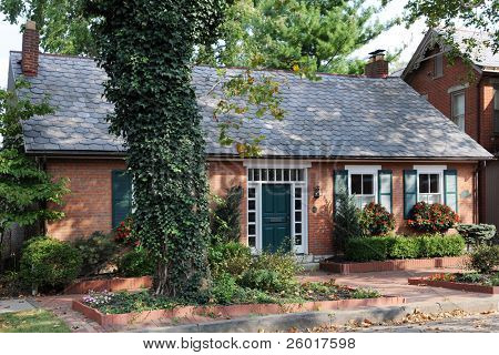An small, well maintained urban brick home in early fall.
