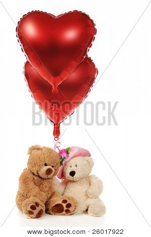 Two snugly Teddy Bears holding 2 red heart-shaped balloons.