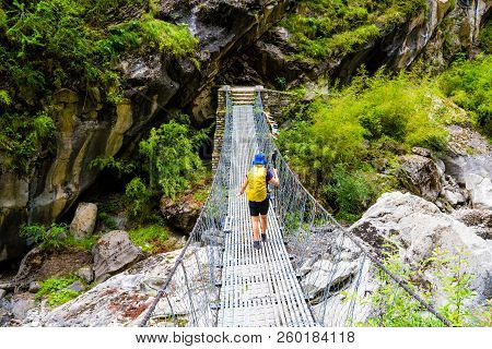 Woman Backpacker On Trekking Path Crossing A Suspended Bridge In Annapurna Conservation Area, Nepal