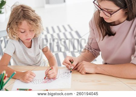 Little Kid Drawing A House Using Colorful Crayons With His Female, Therapist During A Meeting In The