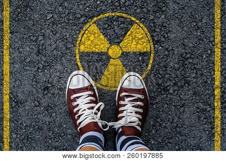 Man Legs In Sneakers Standing On Asphalt Road And Radioactive Sign