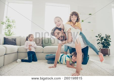 Free Time, Relax, Rest Concept. Little Kids Jump On Daddy Back For Silly Ride On Soft Carpet Floor N