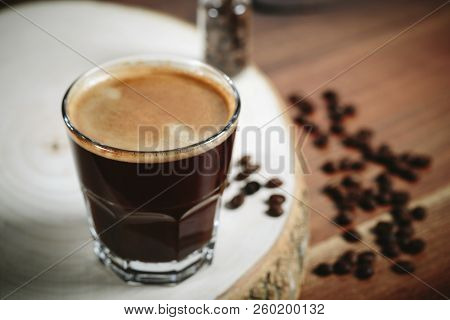 A Cup Of Coffee With Small White Ceramic Dish Full Of Coffee Beans On Wooden Background.