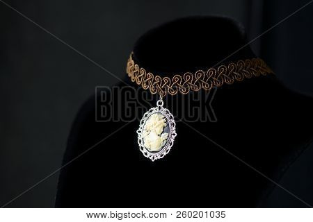 Black velvet choker necklace with rose cameo pendant on a dark background close up poster