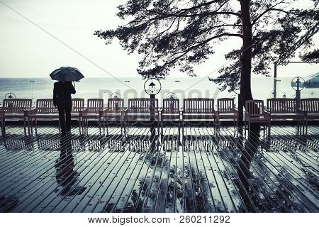 A Man With Umbrella Stands In The Rain On The Coast