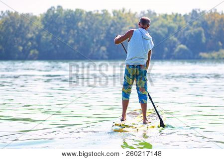Sporty Man Paddling On A Sup Board On Large River And Enjoying Life. Stand Up Paddle Boarding - Awes