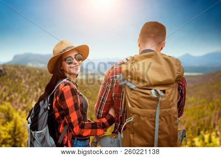 Couple of tourists sitting on the top of mountain
