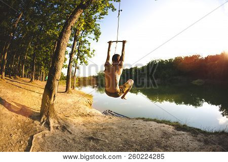 Leap From The Bungee. Jump Into The Water. A Man Is Resting On The Lake. A Swing From A Rope And A S