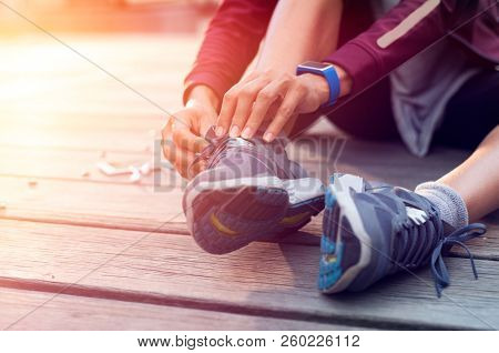 Closeup hand of runner tying laces of her sport shoes. Woman sitting on floor and lacing training sneakers before getting ready for workout.Hands of sportswoman tying shoelaces on sporty sneaker.