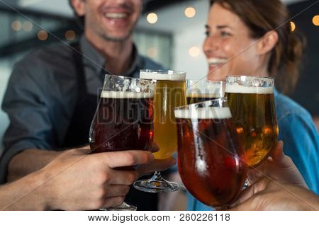 Happy friends clinking glasses of tap beer. Closeup hands of mature men and women toasting with draught beer. People holding beer for raising a toast to celebrate, cheering success with pints of beer.