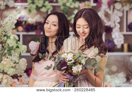 Beautiful Asian Florist Girls Making Bouquet Of Flowers For Sale Against Floral Bokeh Background In