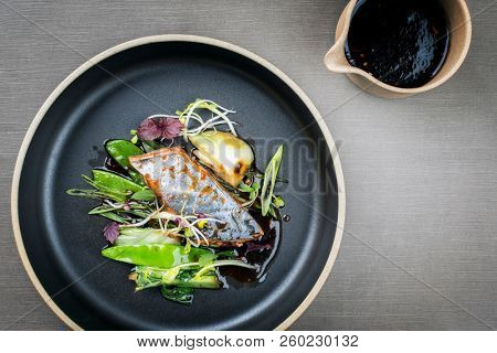 Modern style Japanese bonito tuna fish filet with vegetable glazed in teriyaki sauce as top view on a plate with copy space  poster