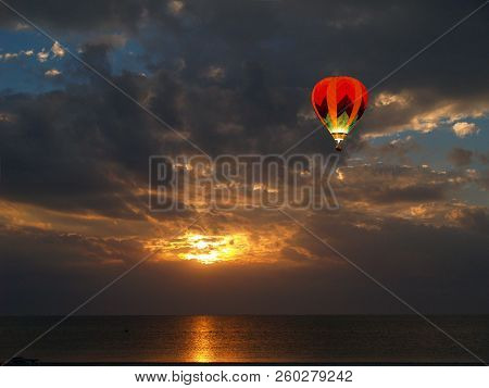 A Beautiful Sun Rise With Clouds And A Hot-air Ballon