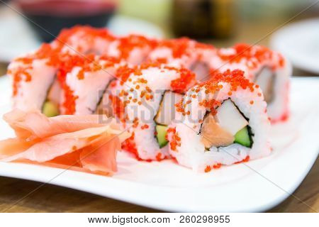 Californian Sushi Rolls With Masago Caviar Near Ginger On White Plate. Japanese Cuisine. Close Up Im