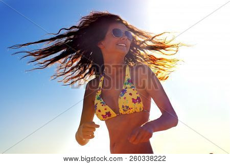 Happy Woman On The Beach. Portrait Of The Beautiful Girl Close-up, The Wind Fluttering Hair. Summer