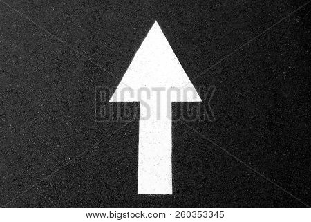 White Road Directions Painted On Black Asphalt