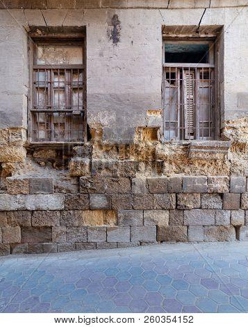Two Adjacent Broken Windows And Grunge Stone Bricks Wall In Abandoned Darb El Labana District, Cairo