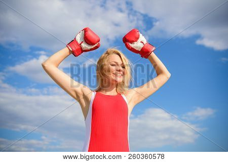 Girl boxing gloves symbol struggle for female rights and liberties. Feminism promotion. Fight for female rights. Girl leader promoting feminism. Woman boxing gloves raise hands blue sky background poster