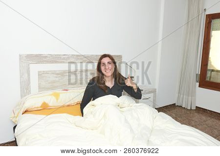 Happy Woman Smiling On Bed With Thumb Up .