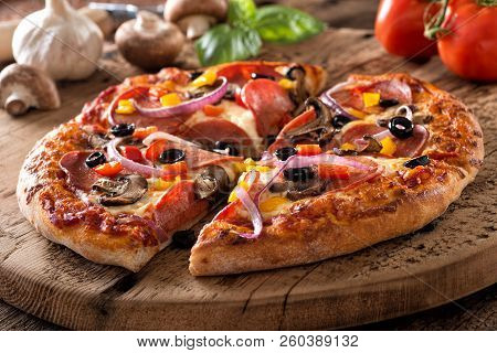 A Rustic Homemade Pepperoni Pizza With Mushrooms, Peppers, Red Onion And Black Olives On A Rustic Bo