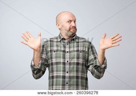 Confused Mature Bearded Man Standing And Shrugging Shoulders Isolated Over White Background.