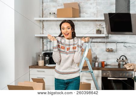 Smiling Young Woman Doing Shrug Gesture In Kitchen During Relocation In New Home