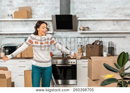 Laughing Young Woman Doing Shrug Gesture In Kitchen With Cardboard Boxes During Relocation In New Ho