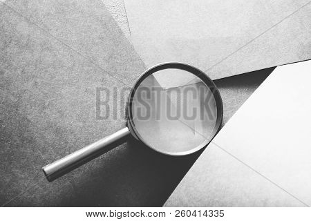 Magnifier On Grey Layered Paper Background. Searching Seeking Looking Recruiting And Headhunting Con