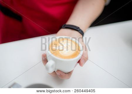 Barista Holds A Cup With A Figurative Coffee Latte In The Form Of An Apple
