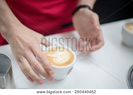 Barista Holds A Cup With A Figurative Coffee Latte In The Form Of An Apple. Hands