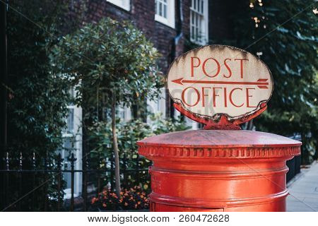 Red Post Box With A Retro Post Office Directional Sign On Top In London, Uk.
