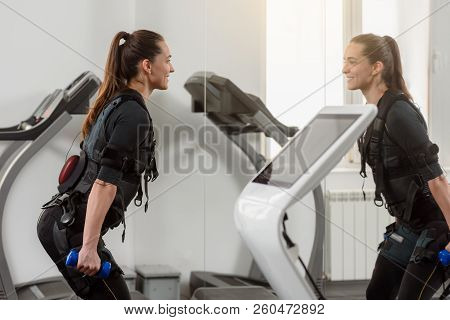 Woman in electro muscular stimulation suit training with dumbbells poster