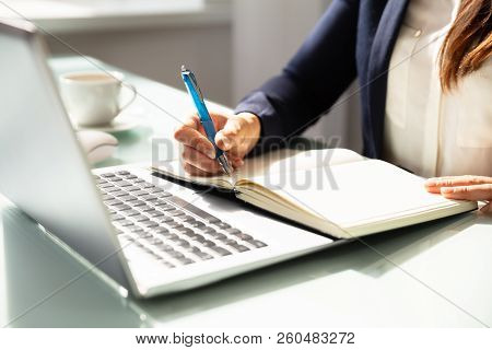 Close-up Of A Businesswoman's Hand Writing Note In Diary