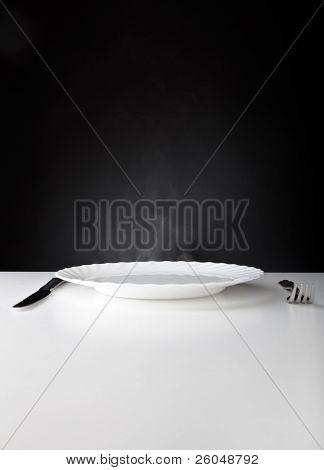 Placa, cuchillo y tenedor sobre fondo blanco y negro