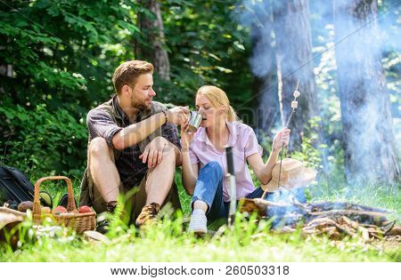 Couple In Love Camping Forest Hike. Food For Hike And Camping. Couple Sit Near Bonfire Eat Snacks An