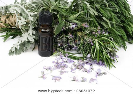 Rosemary and other mediterranean herbs with bottle of essential oil