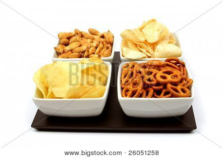 Potato chips and other salty snacks in square bowls isolated on white