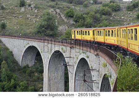 Latour De Carol - September 4, 2018: The Small Yellow Train Of The Pyrenees Crossing A Beautiful Mou