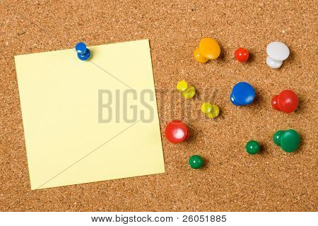 Blank paper note and office pins on cork board