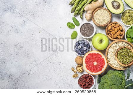 Superfoods On Light Stone Background. Organic Food And Healthy Vegan Food. Legumes, Nuts, Seeds, Avo